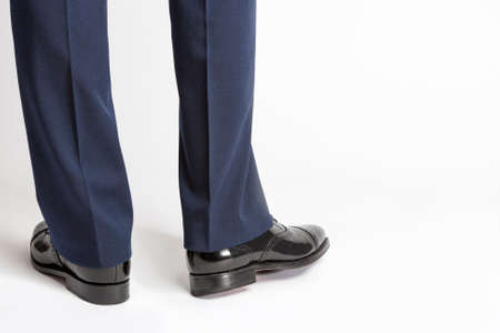 against white: Man in Stylish Black Shiny Male Semi-Brogue Posing In Reversed Position Against White. Horizontal Image Orientation