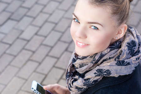 Youth Trends Concept: Closeup of Teenage Caucasian Girl Dealing with Cellphone Outdoor. Horizontal Image Orientation