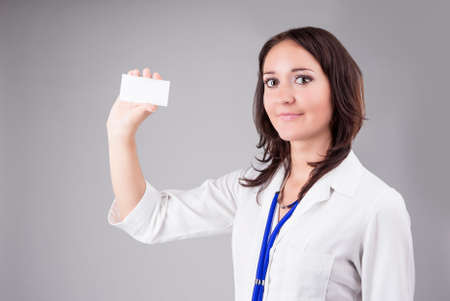 doctor s smock: Young Medical Female Doctor Presenting and Showing White Card for Product or Text. Caucasian Medical Professional Staff Posing Against Gray. Horizontal Image