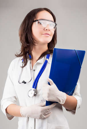doctor s smock: Medical Concept: Caucasian Medical Female Doctor With Stethoscope and Folder. Over Gray Background. Vertical Image Composition