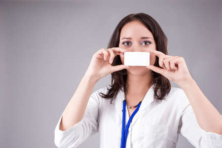 doctor s smock: Young Medical Female Doctor Presenting and Showing White Card In Front of Mouth for Product or Text. Caucasian Medical Professional Staff Posing Against Gray. Horizontal Image Stock Photo