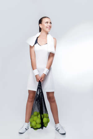 woman s bag: Tennis Sport Concept: Portrait of a Woman With Tennis Balls in Mesh Posing in Studio. Healthy Lifestyles. Vertical Image Orientation
