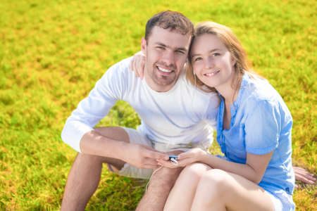 handheld computer: Youth and Family Concepts:Happy Young Caucasian Couple Closeup portrait. Sitting  Outside On Grass Holding Handheld Computer. Listening To Music and Smiling. Horizontal Orientation