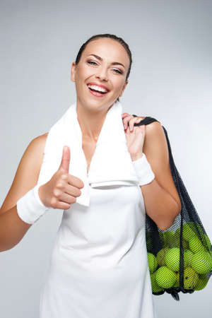 woman s bag: Portrait of Happy Professional Female Tennis Player With Mesh of Balls Against White. Showing Thumbs Up Sign. Vertical Image