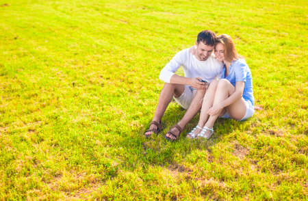 palmtop: Lifestyle Concept: Caucasian Couple Sitting Embraced Together on the Grass Outdoors with Palmtop Handheld. Listening to Music. Horizontal Image Composition