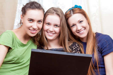 amusment: Three Best Caucasian Girlfriends Sitting Together Embraced with Laptop. Indoors Shot. Horizontal Image Orientation