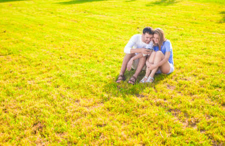 palmtop: Modern Lifestyle Concept: Caucasian Couple Sitting Embraced Together on the Grass Outdoors with Palmtop Handheld. Listening to Music. Horizontal Image Composition