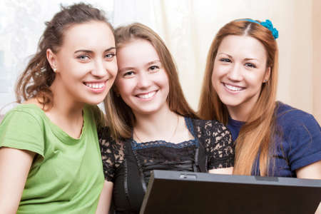 amusment: Happy Lifestyle Concept. Three Best Caucasian Girlfriends Sitting Together Embraced with Laptop. Indoors Shot. Horizontal Image Orientation