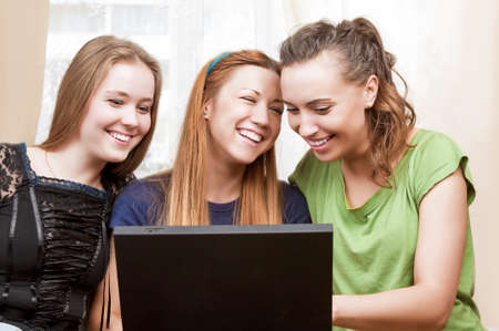 amusment: Friendship Concepts: Three Laughing Caucasian Girls Using Laptop and Having Good Time Together. Horizontal Image Composition Stock Photo