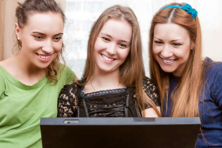 amusment: Modern Lifesrtyle Concept. Portrait of Three Young Happy Laughing Caucasian Girlfriends With Persomal Computer Sitting Indoors. Horizontal Image Orientation