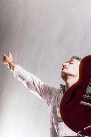 alabanza: Alabanza y Adoración conceptos. Joven caucásico Masculino Guitarrista Adorando. Foto de estudio. Contra Gray. Vertical de la imagen Foto de archivo