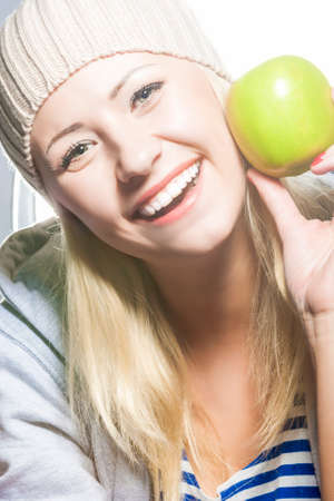 hysterics: Closeup Portrait of Smiling Caucasian Woman With Green Apple.Vertical Image Orientation