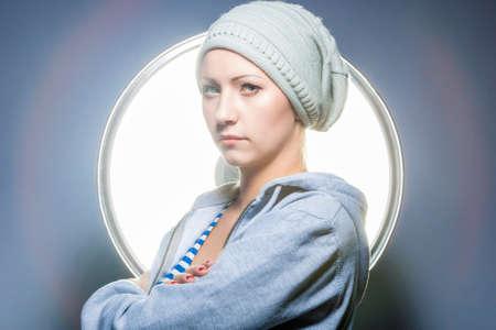 hoody: Fashion Shot of Thinking Caucasian Blond Female in Warm Hat and Wearing Hoody. Posing Against Studio Equipment. Horizontal Image Stock Photo