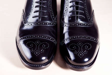 footgear: Style and Mens Fashion Footwear Concept. Pair of New Black Stylish Male Oxfords Laqured Semi-Brouge Laced Shoes. Horizontal Image