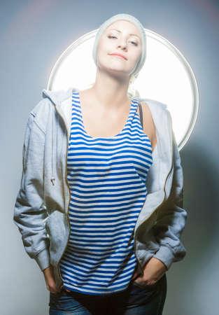 seductress: Fashion Concepts. Nice Portrait of Smiling Positive Caucasian Blond Female Posing Against Studio Environment. Vertical Image Stock Photo