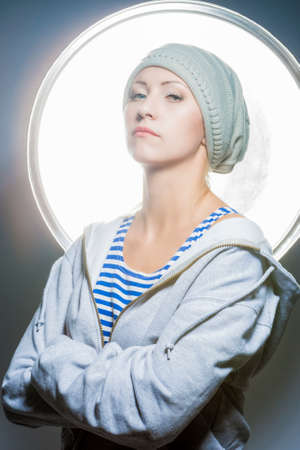 hysterics: Fashion Portrait of Proudly Looking young Caucasian Female in Warm Hat wearing Hoody Jacket. Against Studio Equipment. Vertical Image Composition Stock Photo