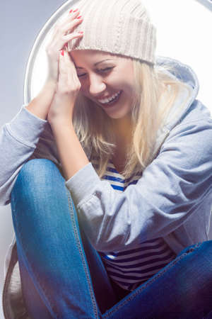 hysterics: Portrait of Happy and Laughing Caucasian Blond Woman in Warm Hat and Hoody. Vertical Image Orientation