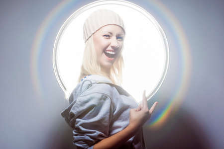 hoody: Young and Sexy Happy Blond Woman Posing in Studio Environment in Hoody and Warm Hat. Horizontal Image