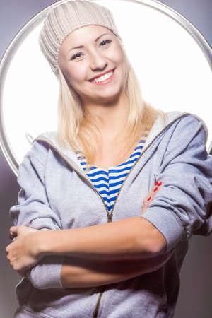 hysterics: Portrait of Smiling Positive Caucasian Blond Female Posing Against Studio Environment. Vertical Image Stock Photo