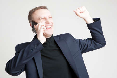 exclaiming: Handsome Caucasian Man In Elegant Siut Speaking Using Cell Phone With Positive Expression.Horizontal Image
