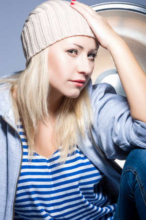 hysterics: Style, Fashion and Glamour Concepts. Nice Portrait of Smiling Caucasian Blond Woman in warm Hat and Hoody in Studio Environment. Vertical Image