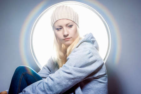 hoody: Portrait of Dreaming Caucasian Blond Woman in Warm Hat and Wearing Hoody Jacket. Horizontal Image orientation Stock Photo