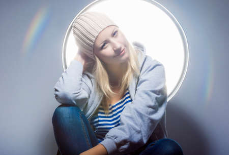 hysterics: Portrait of Dreaming and Smiling Caucasian Blond Woman in Warm Hat and Wearing Hoody Jacket. Horizontal Image orientation