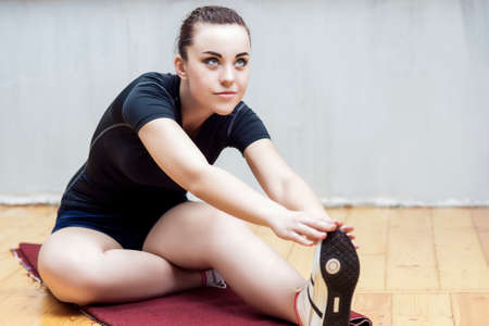 warm up: Sport Ideas and Concepts. Fit Woman Stretching Her Leg to Warm Up  Mussels.Horizontal Image Orientation
