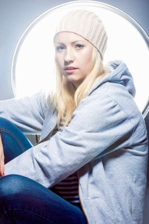sexy image: Proud and Sexy Fashion Caucasian Woman in Sweatshirt and Hoody Against Studio Equipment. Vertical Image Composition