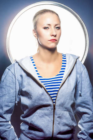 blonde girls: Fashion Concepts. Portrait of Thoughtful Blond Caucasian Female in Hoody Jacket Standing in Studio Environment. Vertical Image