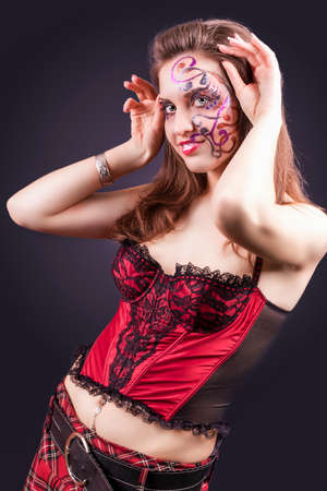 faceart: Face Art Project: Sexy Caucasian Brunette Woman In Corset Painted With Unique Face Art Painting.Against Black Background. Vertical Image Orientation Stock Photo