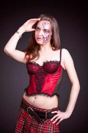 faceart: Face Art Concept: Portrait of Caucasian Female With Unique Face Art Painting. Posing In Corset Against Black.Vertical Image