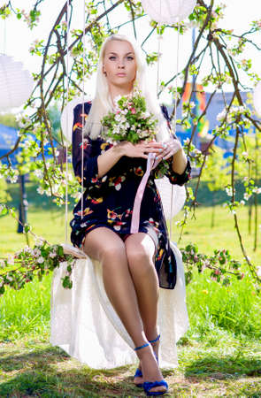 blondy: Beauty Concept: Portrait of Senxy Caucasian Blond With Bunch of Flowers Sitting on Swing Outdoors.Vertical Image
