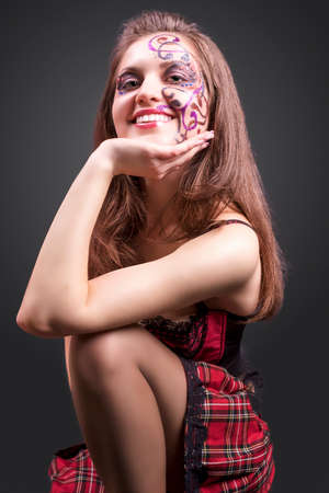 faceart: Portrait of Happy Smiling Caucasian Brunette Woman Painted with Facial Paint with Decorations. Posing Against Black Background. Vertical Image Composition Stock Photo