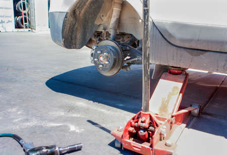 pawl: Automotive Concept: Car Wheel is Being Maintained on Professional Car Repair Station. Horizontal Image Orientation