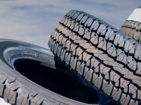new automobile: Closeup of Stack of Brand New Automobile Black Tyres with Numbers Placed Outdoors.