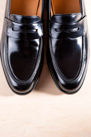 Pair of Stylish Expensive Modern Leather Black Penny Loafers Shoes.Closeup Shot. Vertical Image Concept