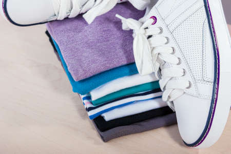 plimsoll: Fashion Ideas and Concepts. Pair of White Fasionable Sneakers Close to Stack of Prepared Clothing. Horizontal Image