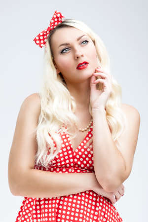 charm temptation: Style Concept. Young Caucasian Blond Female Posing in Pinup Style Against White Background. Isolated Over white Background. Vertical Image