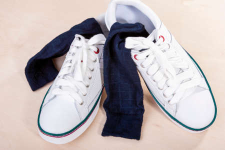 plimsoll: Closeup of Pair of White Trainers with Socks Inserted Inside. Horizontal Image