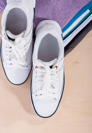 plimsoll: Fashion Ideas and Concepts. Pair of White Fasionable Sneakers Close to Stack of Prepared Clothing. Vertical Image Composition Stock Photo