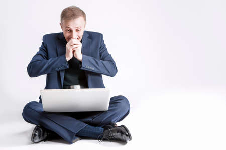 exclaiming: Business Concepts and Ideas. Portrait of Exclaiming and Surprised Caucasian Business Man With Laptop Sitting On Floor. Over White. Horizontal Image Orientation