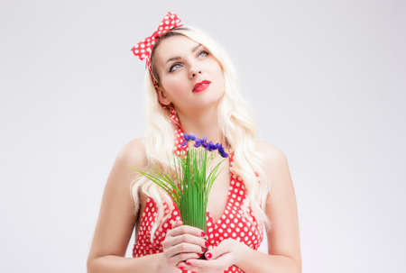polka dotted: Pinup Concepts And Ideas. Sensual Caucasian Blond Female in Red Polka Dotted Dress Dreaming. Holding Bunch of Lilac  Flowers in Hands in Front. Horizontal Image Composition