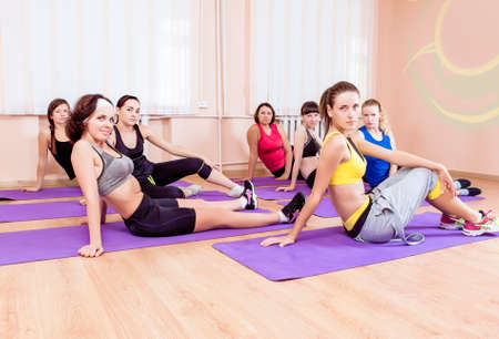 floor mats: Sport, Training anf Healthy Lifestyle Concepts. Group of Seven Caucasian Women Sitting on Floor Mats During Gym Fitness Class. Horizontal Image Orientation