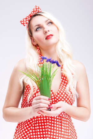 charm temptation: Pinup Concepts And Ideas. Sensual Caucasian Blond Female in Red Polka Dotted Dress Dreaming. Holding Bunch of Lilac  Flowers in Hands in Front. Vertical Image Composition Stock Photo