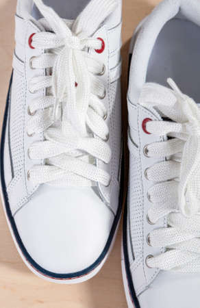 plimsoll: Pair of White Fashionable Laced Trainers On Wooden Surface. Vertical Image Composition