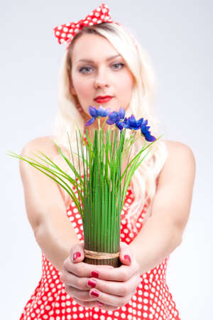 polka dotted: Portrait of Young Caucasian Blond Woman Showing Bunch of Gentle Flowers in Hands In Front. Posing in Red Polka Dotted Dress, Pinup Style.Vertical Image Stock Photo