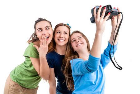photocamera: Three Young Positive Smilig Caucasian Ladies Making Self Photographs With Photocamera. Isolated Over White Background. Horizontal Image Orientation Stock Photo