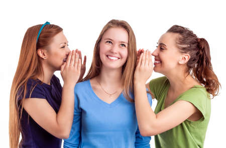 bruit: Portrait of Three Happy Caucasian Females Sharing Secrets and Rumoring To each Other To Ears. Isolated On White Background