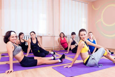 floor mats: Sport, Training anf Healthy Lifestyle Concepts. Group of Seven Caucasian Women Resting on Floor Mats During Gym Fitness Class. Horizontal Image Orientation Stock Photo